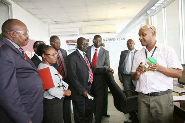 TBL Dar es Salaam production plant officer, Kelvin Nkya (R) gives factory tour to Kenya Military officers dressed in civilian attire in December, 2014 (Photo Credit: Muhidini Michuzi)
