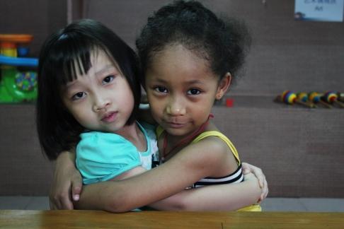 Amina Magasaga (right) hugs a friend at the Huiling Integrated Kindergarten, in Baiyun. Photo Credit: Jenni Marsh