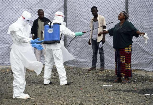 Medical personel disinfect a person suspected to have the ebola virus in Liberial