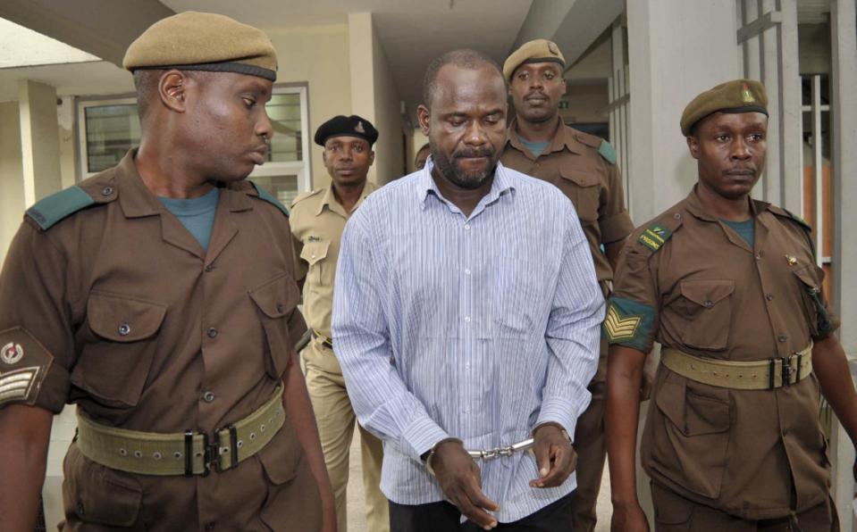 Jamil Mukulu (in whie shirt) under police escort at Kisutu Resident Magistrate's Court in Dar es Salaam. Photo credit: K-Vis Blog