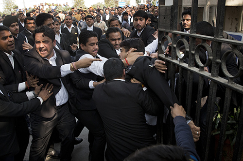 Lawyers scuffle outside a Delhi court on Wednesday. Several journalists say they were beaten by lawyers at the court in the past week. (AP/Tsering Topgyal)