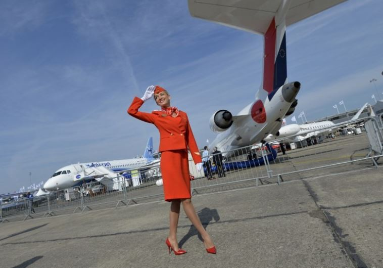 A flight attendant salutes to visitors during the International Paris Airshow at Le Bourget. (photo credit:AFP PHOTO)