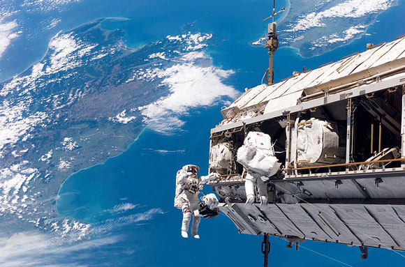 Astronauts Robert Curbeam, Jr. and Christer Fuglesang working on the International Space Station.