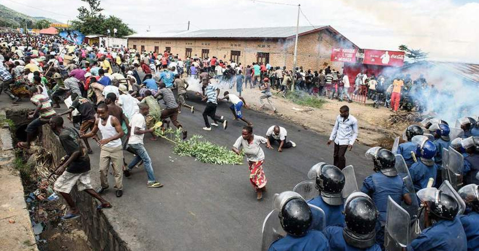 Burundi policemen and army forces face protestors during a demonstration against incumbent president Pierre Nkurunzizas bid for a 3rd term on 13 May 2015 in Bujumbura. In the neighborhood of Musaga, hundreds of people waved sticks and threw stones as police responded with tear gas, a water cannon and live rounds. (AFP/Jennifer Huxta)