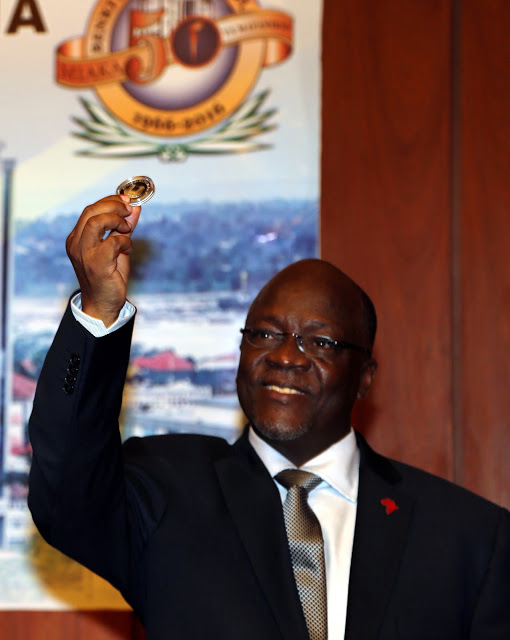 President Johm Pombe Magufuli launches the new Tsh. 50,000 coin at the Bank of Tanzania June 22, 2016 during celebrations to mark the Banks 50th anniversary and poses the question, Where is the money?