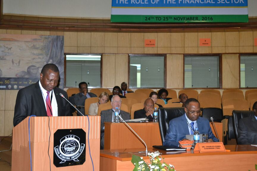 Planning and Finance Minister Dr. Philip Mpango (Left) Delivers opening Speech at Financial Institutions Conference in Arusha as Tanzania Bankers Association Chairman Dr. Charles Kimei Sits to Minister's left at Front row.