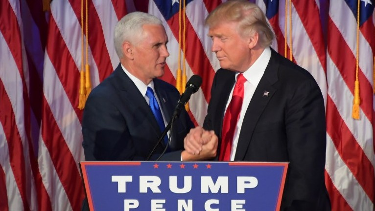 Republican president-elect Donald Trump (R) shakes hands with his running mate Mike Pence at the New York Hilton Midtown in New York on November 9, 2016. (AFP/Jim Watson)