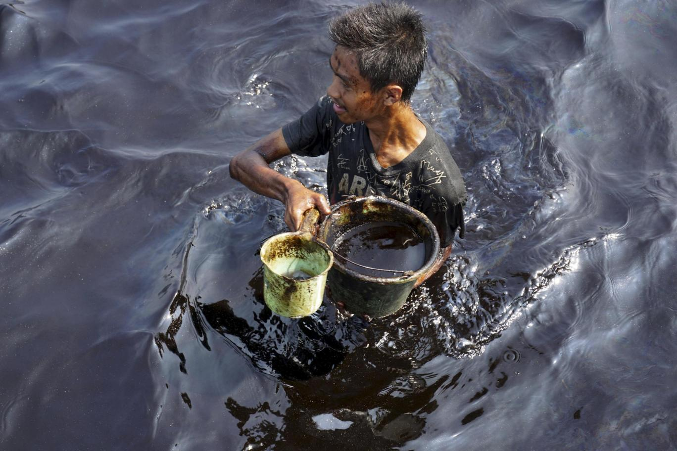 A fisherman collects spilled crude oil at the Pantai Teluk Penyu in Cilacap, Indonesia Reuters